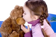 A sweet baby girl kiss her teddy. And smiles Royalty Free Stock Photos