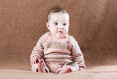 Sweet baby girl in knitted suit sitting on a camel Stock Photography