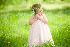 Sweet baby girl outdoors with a bouquet of lilies Royalty Free Stock Photo