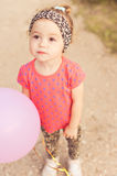 Sweet baby girl with pink balloon outdoors Royalty Free Stock Image