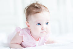 Sweet baby girl in a pink dress playing on her tummy Stock Photo