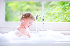 Sweet baby girl playing with foam in big kitchen sink. Funny little baby girl with wet curly hair taking a bath in a kitchen sink with lots of foam playing with stock image
