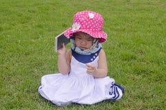 Sweet baby girl playing mobile phone Stock Photo