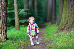 Sweet baby girl in rain jacket walking in autumn p Royalty Free Stock Photography
