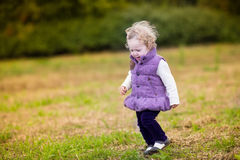 Sweet baby girl running in colorful autumn park Stock Photo