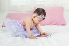 Sweet baby girl sitting on bed at home. Stock Photos