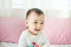 Sweet baby girl sitting on bed at home. Royalty Free Stock Images