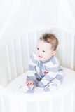 Sweet baby girl sitting in a round white bassinet Stock Photography