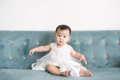 Sweet baby girl sitting on the sofa at home. Royalty Free Stock Photography