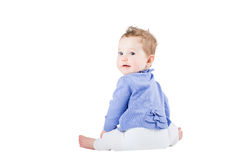 Sweet baby girl sitting and watching over her shoulder Royalty Free Stock Photos