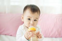 Sweet baby girl sucking milk in bottle at home. Sweet baby girl sucking milk in bottle at home Royalty Free Stock Image