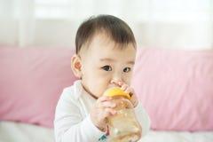 Sweet baby girl sucking milk in bottle at home. Sweet baby girl sucking milk in bottle at home Stock Image