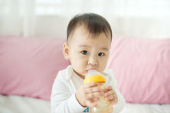 Sweet baby girl sucking milk in bottle at home. Sweet baby girl sucking milk in bottle at home Stock Photos