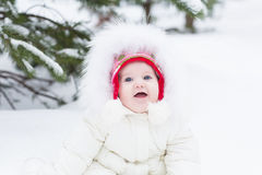 Sweet baby girl in white jacket sitting under snowy christmas tree Royalty Free Stock Photo