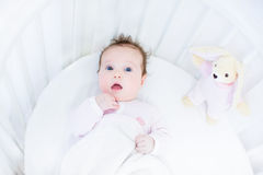Sweet baby girl in a white round crib with pink bunny toy Stock Photo