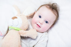 Sweet baby girl in a white round crib with pink bunny toy Stock Photos