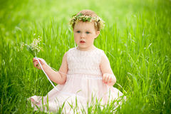 Sweet baby girl in wreath of flowers sitting on green grass Royalty Free Stock Photos