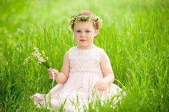 Sweet baby girl in wreath of flowers sitting on green grass Stock Image