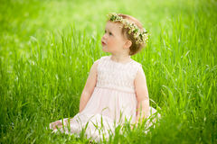 Sweet baby girl in wreath of flowers sitting on green grass Royalty Free Stock Image