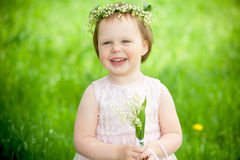 Sweet baby girl in wreath of flowers smiling Stock Image