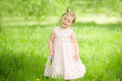 Sweet baby girl in wreath of flowers smiling Stock Photos