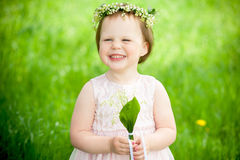 Sweet baby girl in wreath of flowers smiling Stock Photography