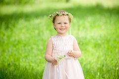 Sweet baby girl in wreath of flowers smiling Royalty Free Stock Photography
