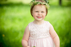 Sweet baby girl in wreath of flowers smiling outdoors Royalty Free Stock Images