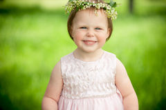 Sweet baby girl in wreath of flowers smiling outdoors Stock Photography