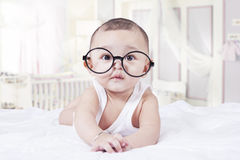 Sweet baby with glasses in bedroom Stock Photo