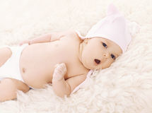 Sweet baby in hat yawns on the bed Stock Photo