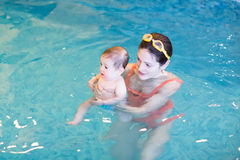 Sweet baby with her mother in early swimming class. Sweet little baby with her mother in early swimming class stock images