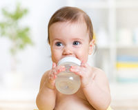 Sweet baby holding bottle and drinking water Stock Image