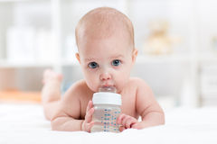 Sweet baby holding bottle and drinking water Stock Photos