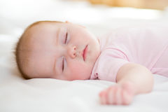 Sweet baby infant lying on a bed while sleeping in a bright room. Peaceful baby lying on a bed while sleeping in a bright room Stock Photography