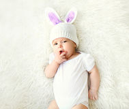 Sweet baby in knitted hat with a rabbit ears lying on bed Stock Image