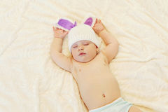 Sweet baby in knitted hat with a rabbit ears sleep on bed Stock Image