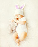 Sweet baby in knitted hat with a rabbit ears and teddy bear toy. Lying on bed, top view Royalty Free Stock Photography