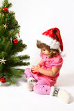Sweet baby and a New Year or Christmas tree. Sweet baby decorate the New Year or a Christmas tree royalty free stock images