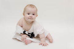 Sweet baby. A nice baby in a sport shirt sits on the floor royalty free stock image