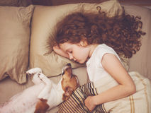 Sweet baby and puppy is sleeping in night. Stock Photo