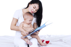 Sweet baby reading story book with mom Stock Photos
