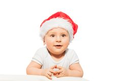 Sweet baby in red Christmas hat stands looking Royalty Free Stock Photo
