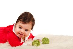 Sweet baby in santa dress smiling with two green baubles Royalty Free Stock Images