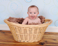 Sweet baby sitting with big smile in wicker basket Royalty Free Stock Photos