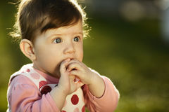 Sweet baby sitting on grass in garden Stock Images