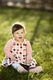 Sweet baby sitting on grass in garden Royalty Free Stock Photos
