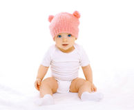 Sweet baby sitting in the pink knitted hat. Portrait of sweet baby sitting in the pink knitted hat Royalty Free Stock Photos