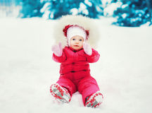 Sweet baby sitting on the snow in winter Royalty Free Stock Photos