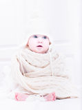 Sweet baby sitting in a white nursery in a huge hat and knitted scarf Stock Photos